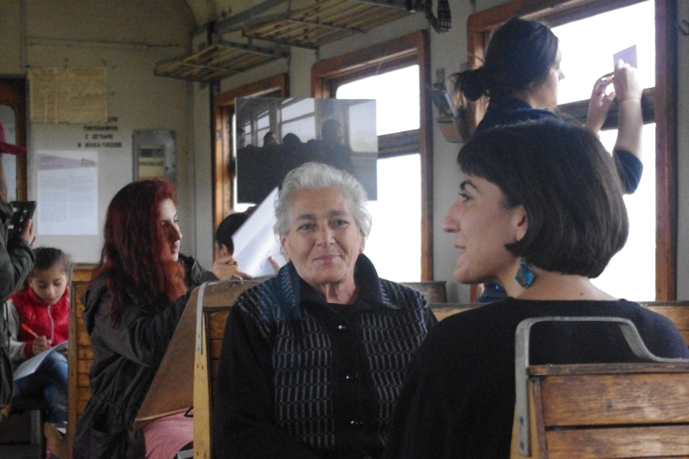 "Curator Anna Gargarian talks with a passenger about ""In Motion."" Photo credit: Setrag Shahikian"